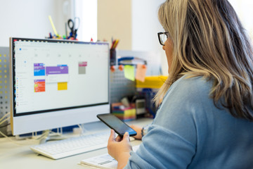 Female child therapist in an office during a phone call, using online calendar to schedule patients appointments. Calendar Planner Organization Management Concept.