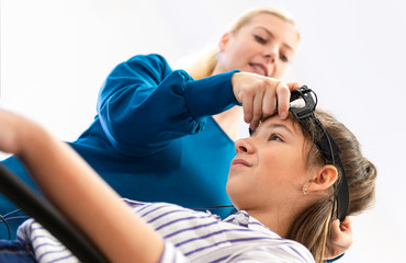 Young teenage girl and child therapist during EEG neurofeedback session. Electroencephalography concept.
