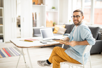 Happy young casual businessman with notepad sitting on chair by desk and working over new business project