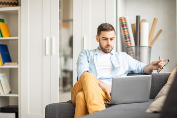 Young confident businessman in casualwear sitting on sofa in front of laptop at home and searching for online information