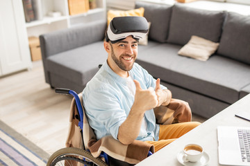 Happy young businessman with vr headset on forehead showing thumbs up while looking at you with smile
