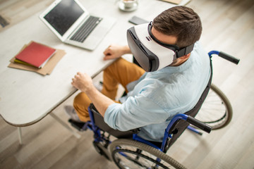 Disable man with vr headset sitting on wheelchair by desk with laptop and documents while working with virtual stuff