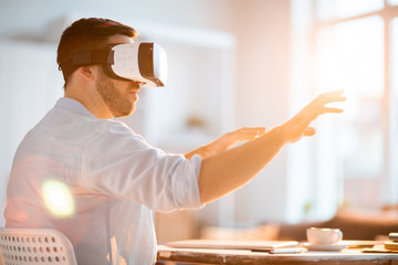 Young businessman with vr headset sitting by workplace with his arms in front of himself while looking through virtual stuff