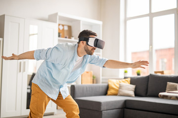 Young man in casualwear looking at virtual stuff in vr goggle while moving with stretched arms at home