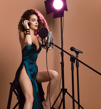 Beautiful singing girl curly afro hairstyle. Beauty woman singer sing with microphone karaoke song in modern green emerald dress