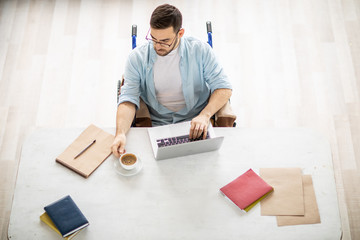 Young handicapped man in casualwear sitting by desk in front of laptop and having coffee while organizing work