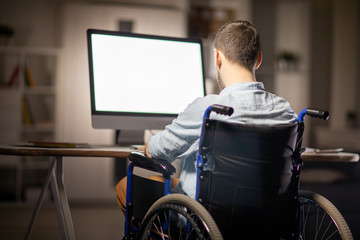 Back view of handicapped businessman sitting in wheelchair by desk in front of computer monitor and concentrating on work