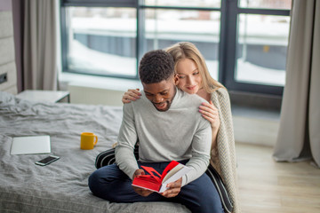 Young, attractive mixed-race couple sit together on bed and read a book together. Caucasian blonde woman wearing warm wrap on shoulders, embracing her african friend from the back