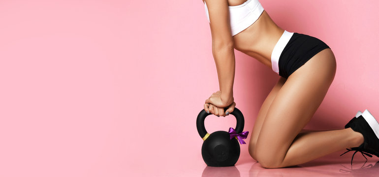 Fitness Girl working out with big weight dumbbell happy smiling on pink. Sport work out concept for woman day 8 march