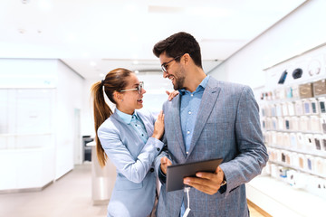 Happy multicultural couple in formal wear buying new tablet while standing in tech store. Man holding tablet while woman leaning on him.