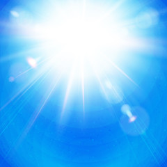 Bright Sunburst with radiating rays in a clear blue sky.