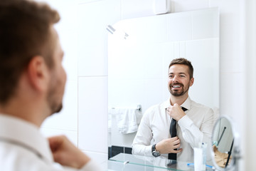 Smiling businessman putting on necktie while looking in the mirror and standing in the bathroom.