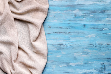 Sand color napkin on blue wooden table top view with copy space