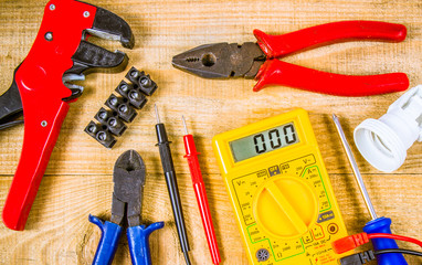Electrical tester and other tools of electrician on a wooden background.