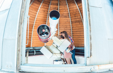 Kids looking through telescope in public star observatory