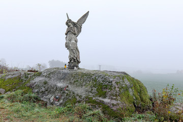 Lone statue of an angel in the fields