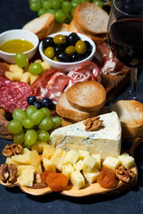 cheese platter on a wooden board, bread, fruit and cold cuts on dark background, vertical closeup