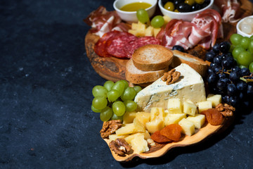 cheese platter on a wooden board, bread, fruit and cold cuts on dark background