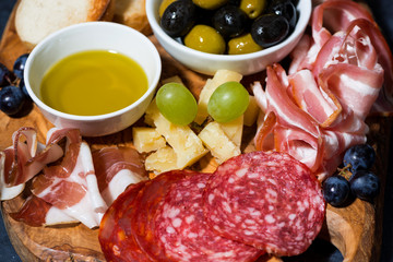 cold cuts, bread and cheese on wooden board, closeup