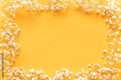 Bright yellow paper background with soft little white flowers, welcome spring concept. Happy Mother's Day, Women's Day, Valentine's Day or Birthday greeting card template.