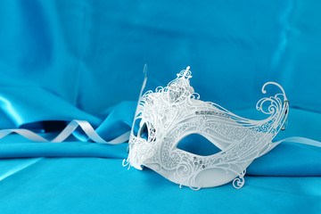 Photo of elegant and delicate white lace venetian mask over light turquoise silk background.