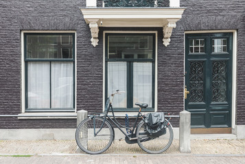 Typical Amsterdam old town street view in Netherlands with old doors and windows and vintage bicycle, front view horizontal daytime picture