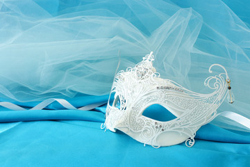 Photo of elegant and delicate white lace venetian mask over light turquoise silk and chiffon background.