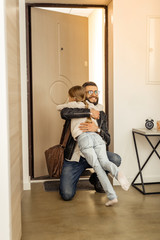 Attractive tall short-haired bearded man from generation Y hugging his daughter