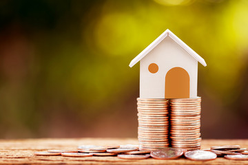 Fototapeta Loan or saving money for buy a house and real estate for family concept, Home model put on the stack coin tower with growing business investment in the in the public park. obraz