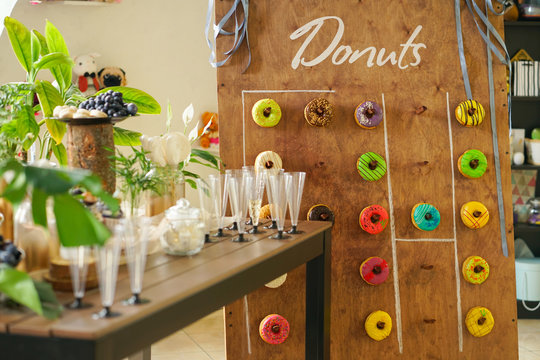 assortment of colorful fresh donuts on a wooden Board for the holiday