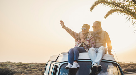 Travel and enjoying life lifestyle in love for couple in relationship sitting on the roof of a old vintage romantic van with sunset and sunlight golden tones background - forever together wanderlust  Wall mural