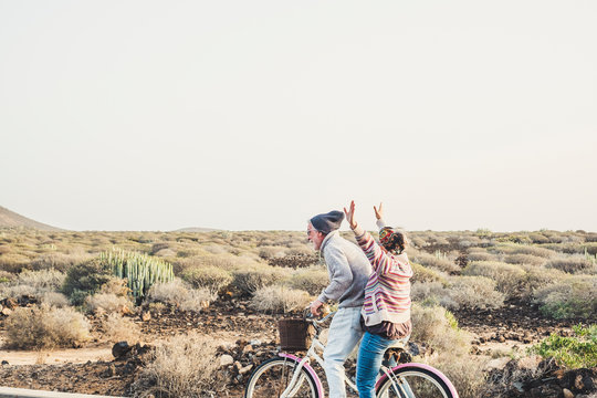 Caucasian aged mature couple have a lot of fun riding together the same bike in outdoor happy leisure activity together in relationship and forever concept - enjoy lifestyle and never end happiness