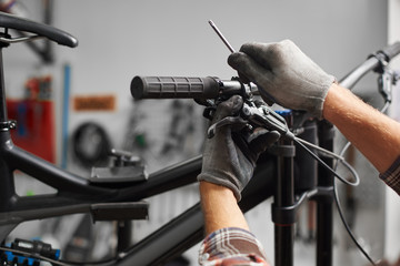 Cropped shot of male mechanic working in bicycle repair shop, worker fixing mountain bike using special tool, wearing protective gloves Fototapete