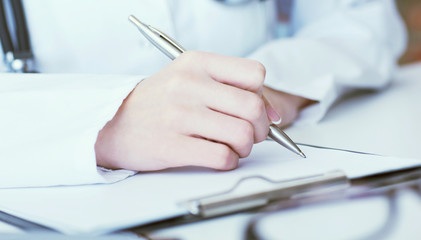 Female medicine doctor hand holding silver pen writing something on clipboard closeup.