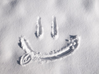 Smile emoji painted on the snow, close-up, top view