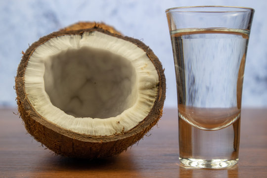 Transparent coconut liquor in a stack and half a coconut