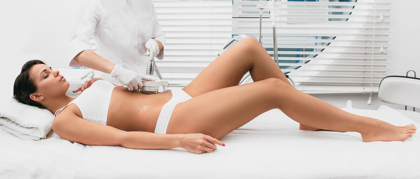 Beautiful woman having cavitation, procedure removing cellulite on her abdomen at beauty clinic