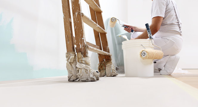 painter man at work with a roller, bucket and scale, from below view, copy space template