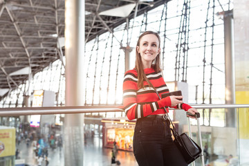 Portrait of a beautiful happy young traveler girl with a suitcase holding a passport in her hands is enjoying a long trip to far warm countries