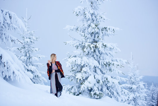 Attractive woman in short embroidered and decorated sleeveless fur coat made from sheepskin on snowy spruce trees blurred background. Traditional women's attire of western part of Ukraine.