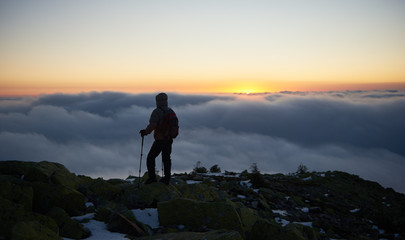 Back view of tourist in warm jacket with backpack and hiking sticks on rocky mountain peak enjoying view of valley covered with white clouds stretching to horizon and bright morning sky at sunrise.