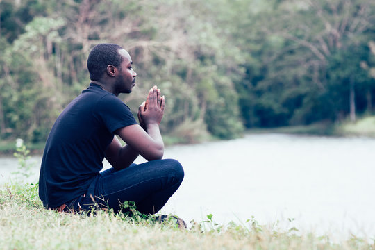 African man praying for thank god with green nature in background.