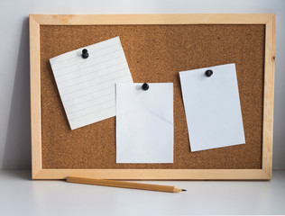 three blank sheets of paper attached to the cork Board with a push button