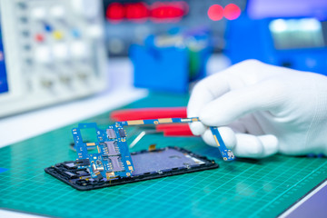 Repairing the smartphone's motherboard in the lab.