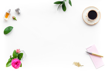 Home work desk, feminine workplace. Notebook and stationery near pink flowers and coffee on white background top view copy space frame