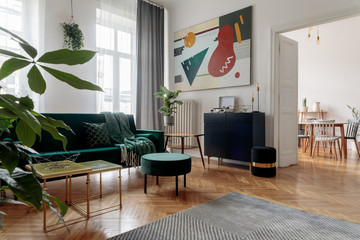 Luxury and modern home interior with design furniture, armchair, tables, pouf and accessroies. View on the dinning room. Stylish decor of sitting room.