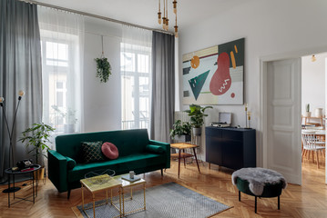 Luxury and modern home interior with design furniture, coffee tables, pouf, lamps and accessories. Next to the dinning room. Stylish decor of living room. Brwon wooden parquet and grey curtains.