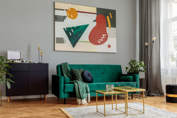 Luxury and modern home interior with design green sofa, navy commode, coffee tables, lamp, pouf and accessroies. Abstract painting. Stylish decor of living room with brown parquet.