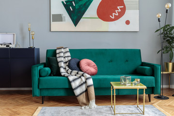 Luxury and stylish interior with green velvet design sofa, coffee table, lamp and commode. Grey walls with abstract painting. Stylish decor of sitting room. Brown wooden parquet.