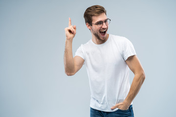 Portrait of a happy young man pointing fingers up at copy space isolated over gray background.